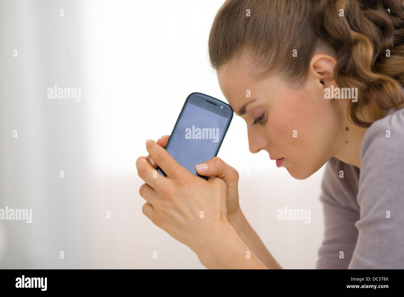 Portrait of stressed young woman with cell phone - Stock Image
