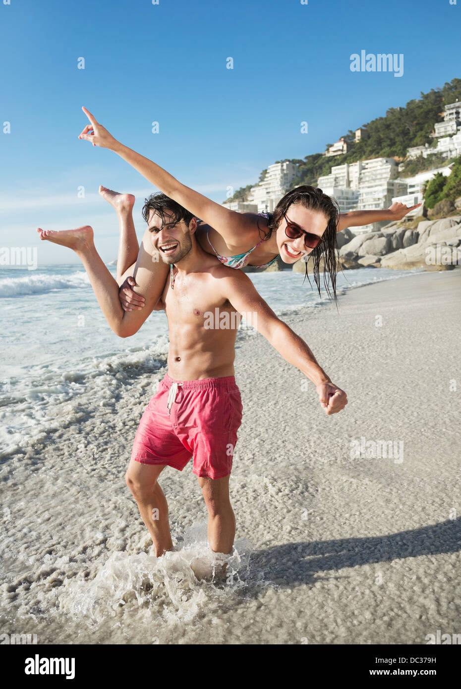 Portrait of happy man lifting woman on beach - Stock Image