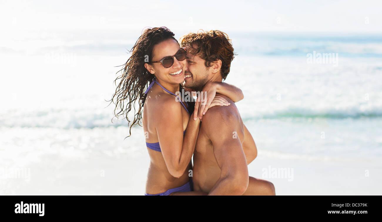 Enthusiastic couple hugging on beach - Stock Image