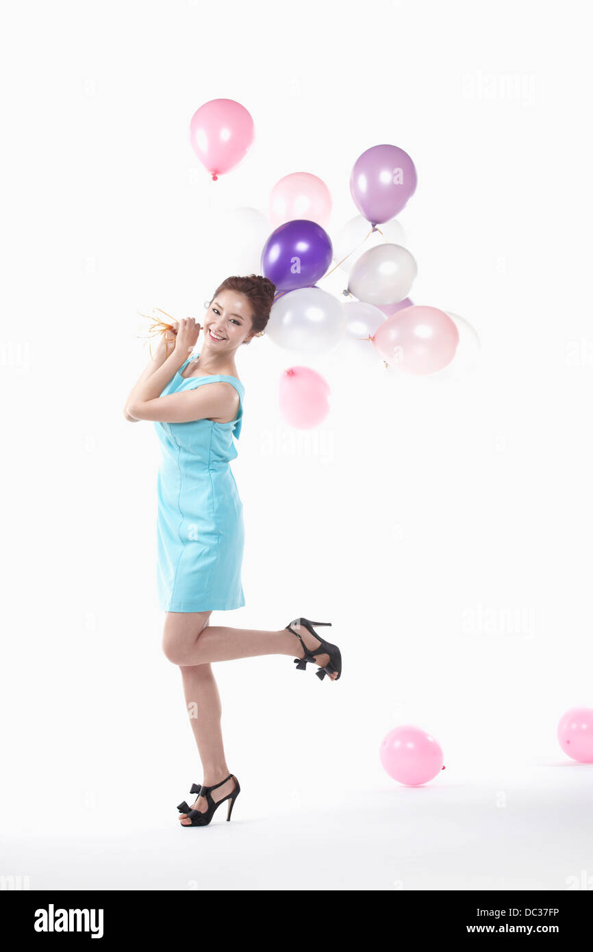 a lady in mini dress posing with balloons - Stock Image