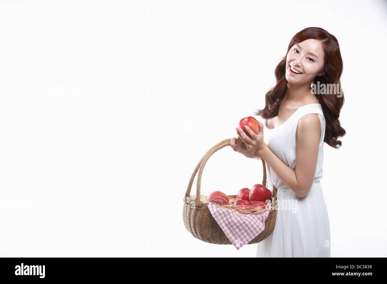 a lady in white dress holding a basket of apples - Stock Image