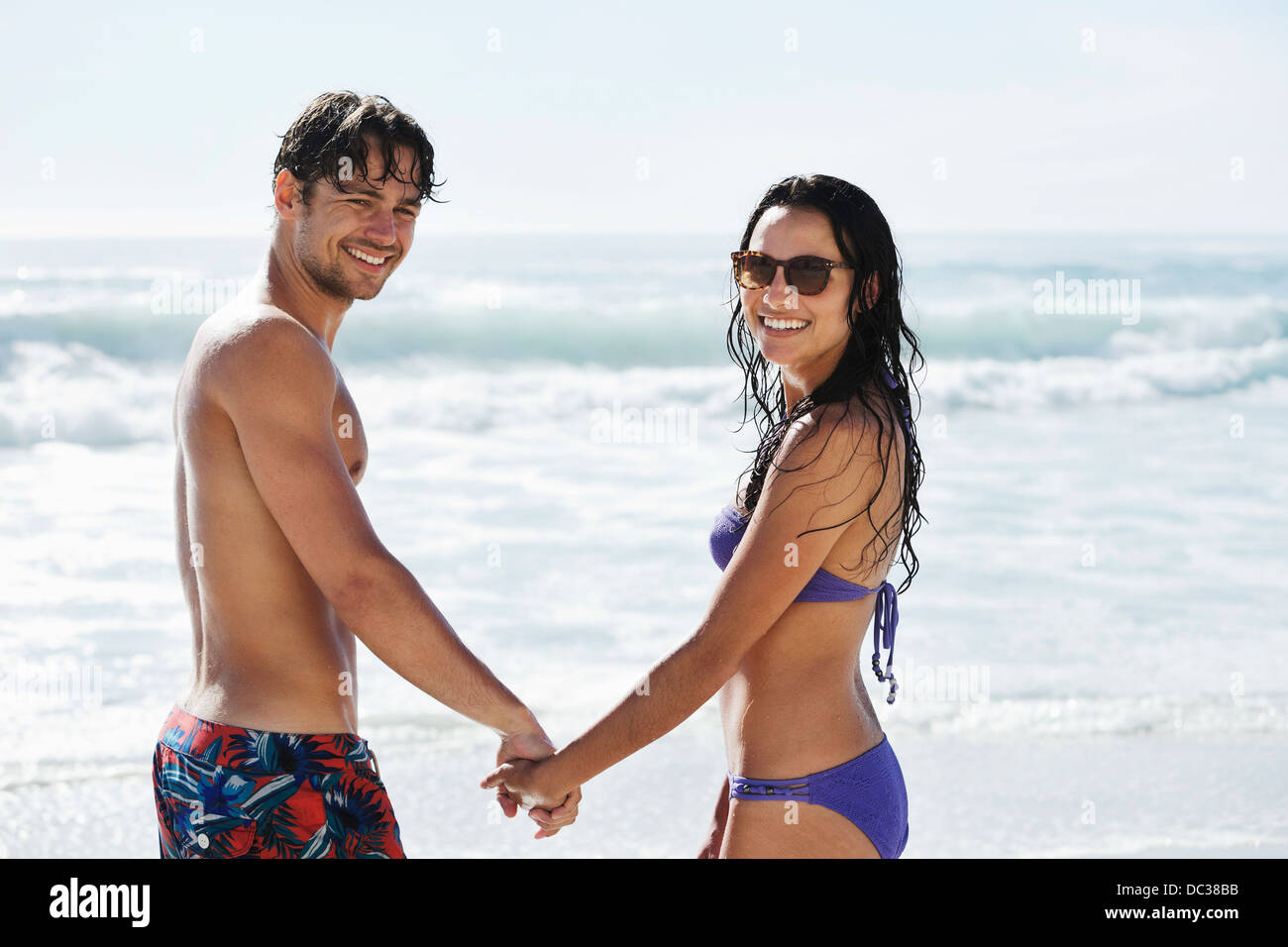 Portrait of happy couple holding hands on beach - Stock Image