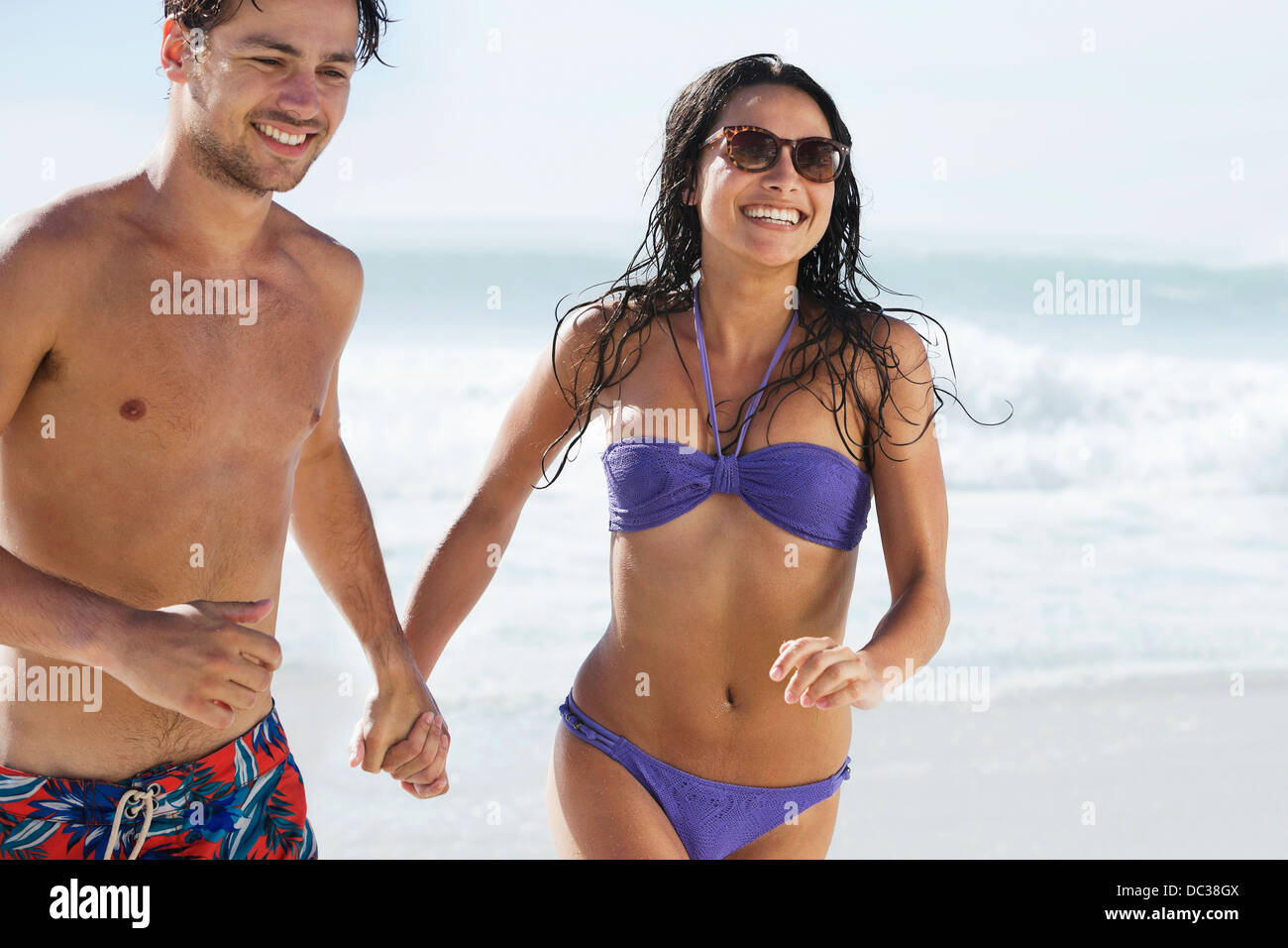 Happy couple holding hands and running on beach - Stock Image