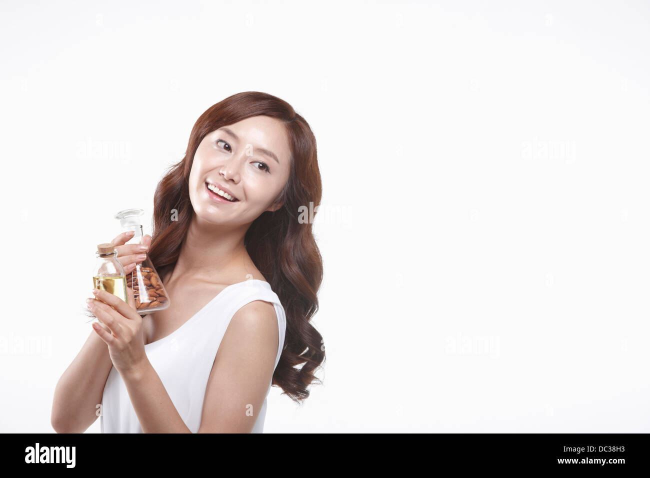 a lady in white dress holding a jar with nuts - Stock Image