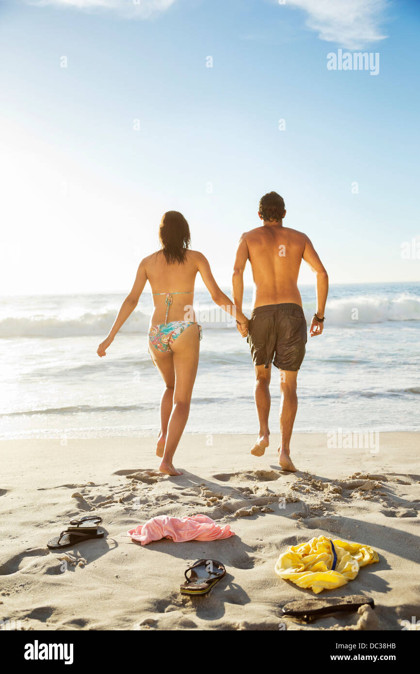 Couple holding hands and walking toward ocean on beach - Stock Image