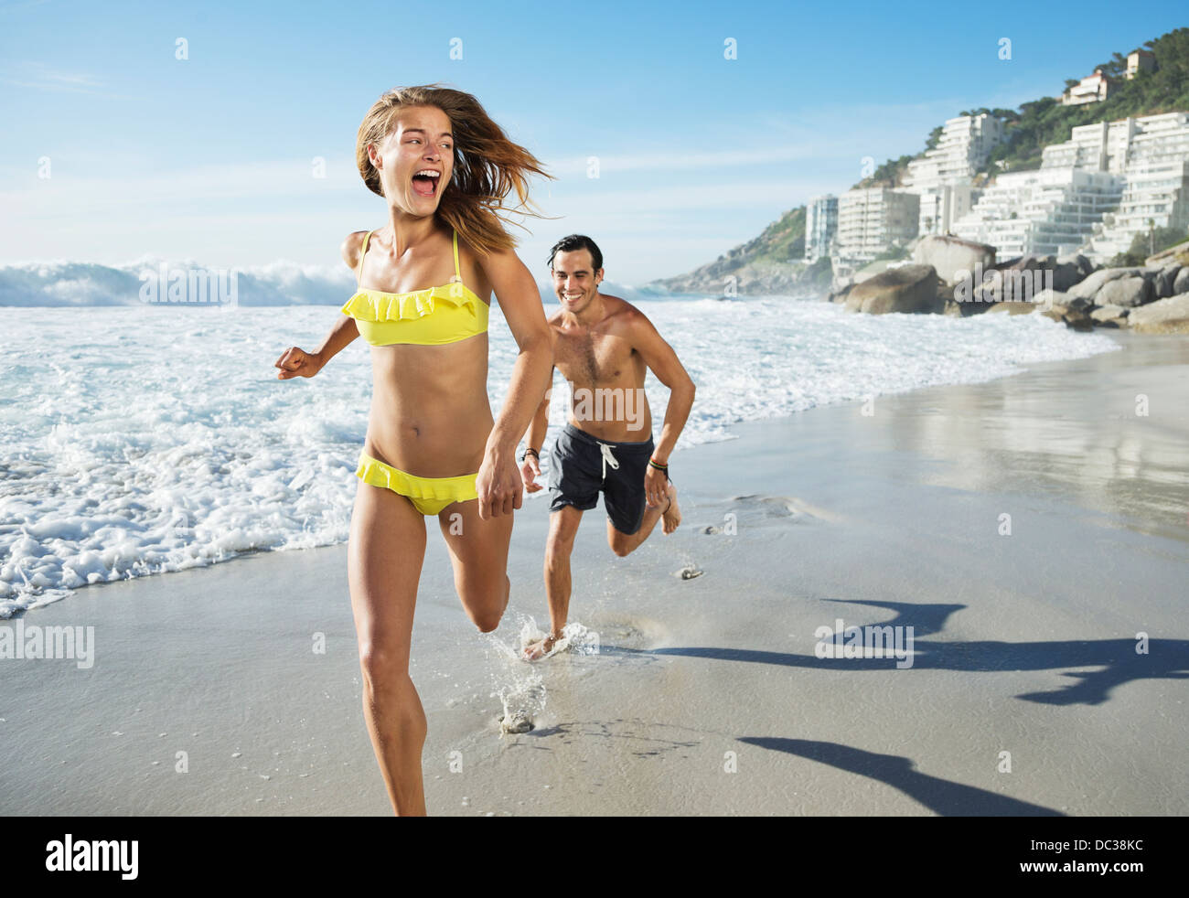 Man chasing happy woman on beach - Stock Image