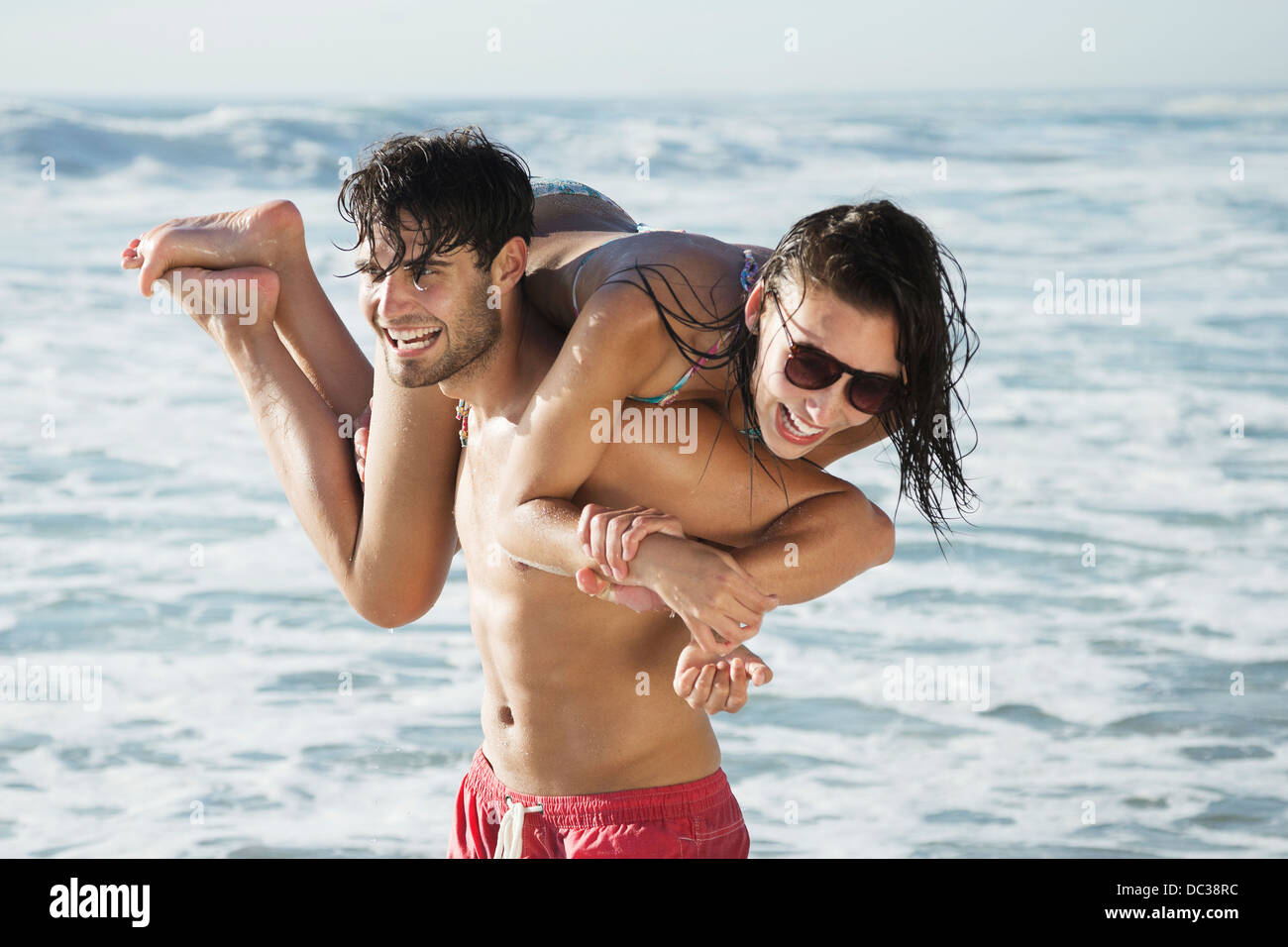 Happy man carrying woman on beach - Stock Image