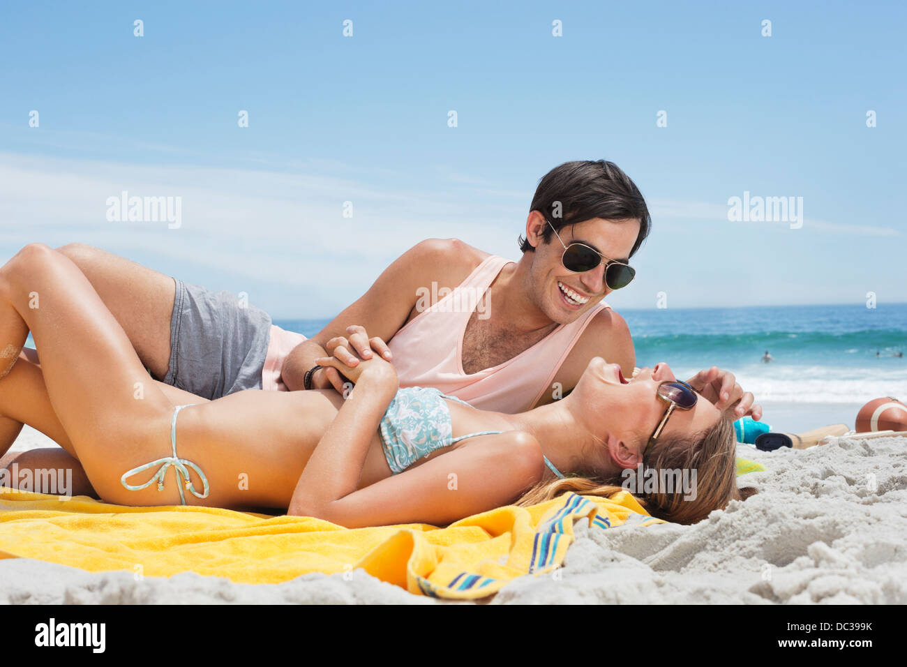 Happy couple laying on blanket at beach - Stock Image