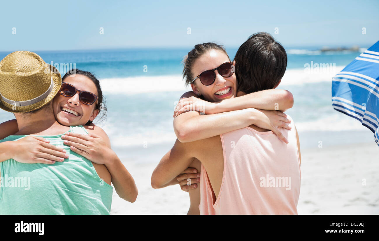 Happy couples hugging at beach - Stock Image