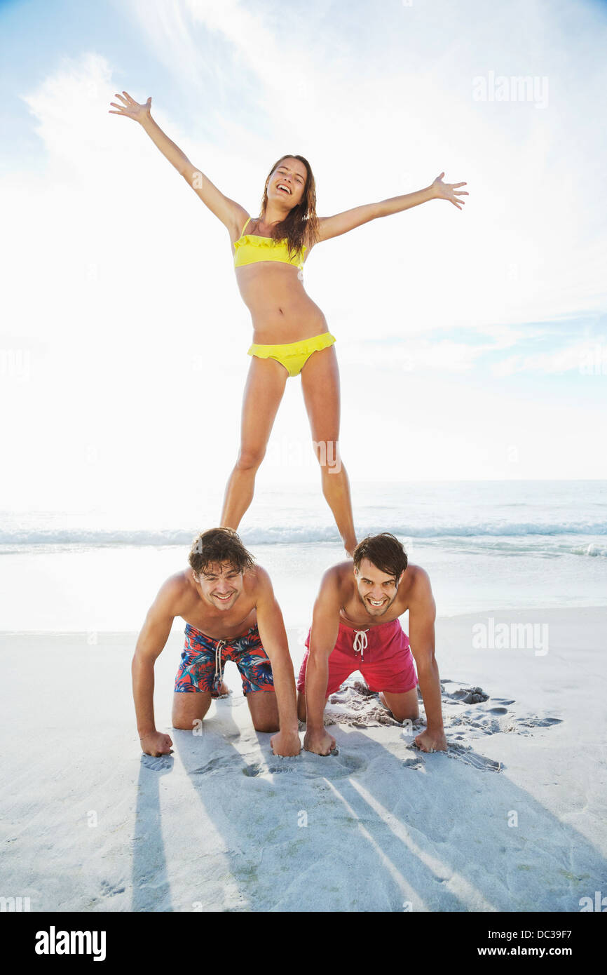 Portrait of woman standing on men's back on beach - Stock Image