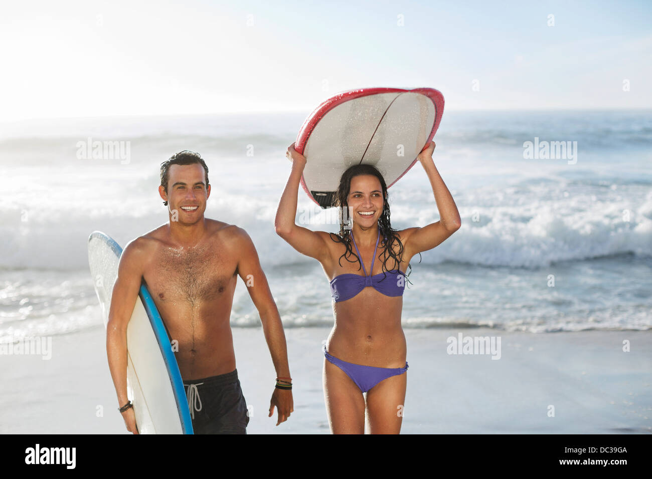 Happy couple carrying surfboards at beach - Stock Image