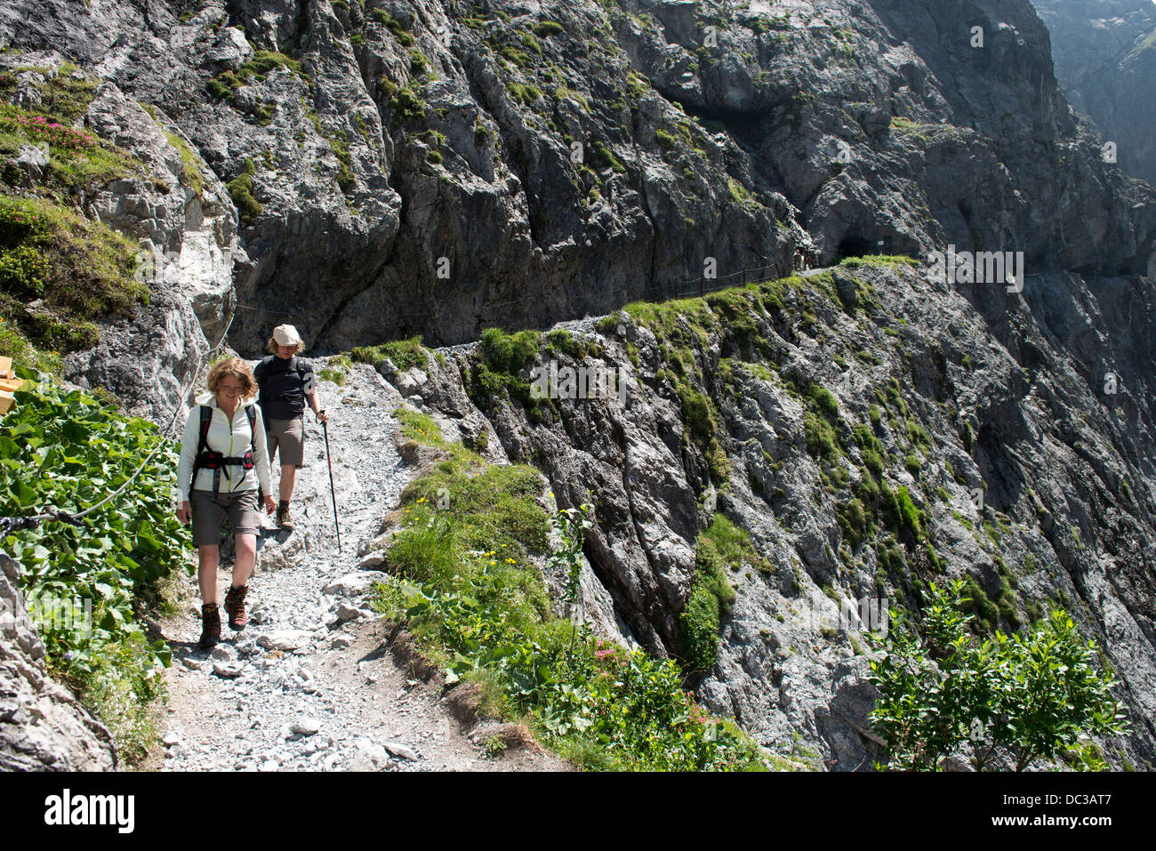Wanderer auf Felsenweg in der Uinaschlucht - Hiker  on steep rock trail, Val d Uina Stock Photo