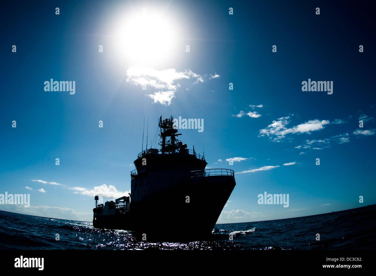supply vessel silhouette back lite offshore hard sun - Stock Image