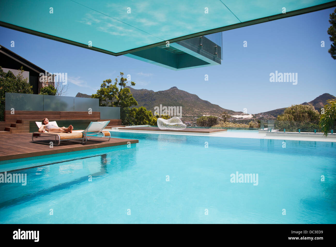 Woman sunbathing on lounge chair at poolside with mountain view Stock Photo