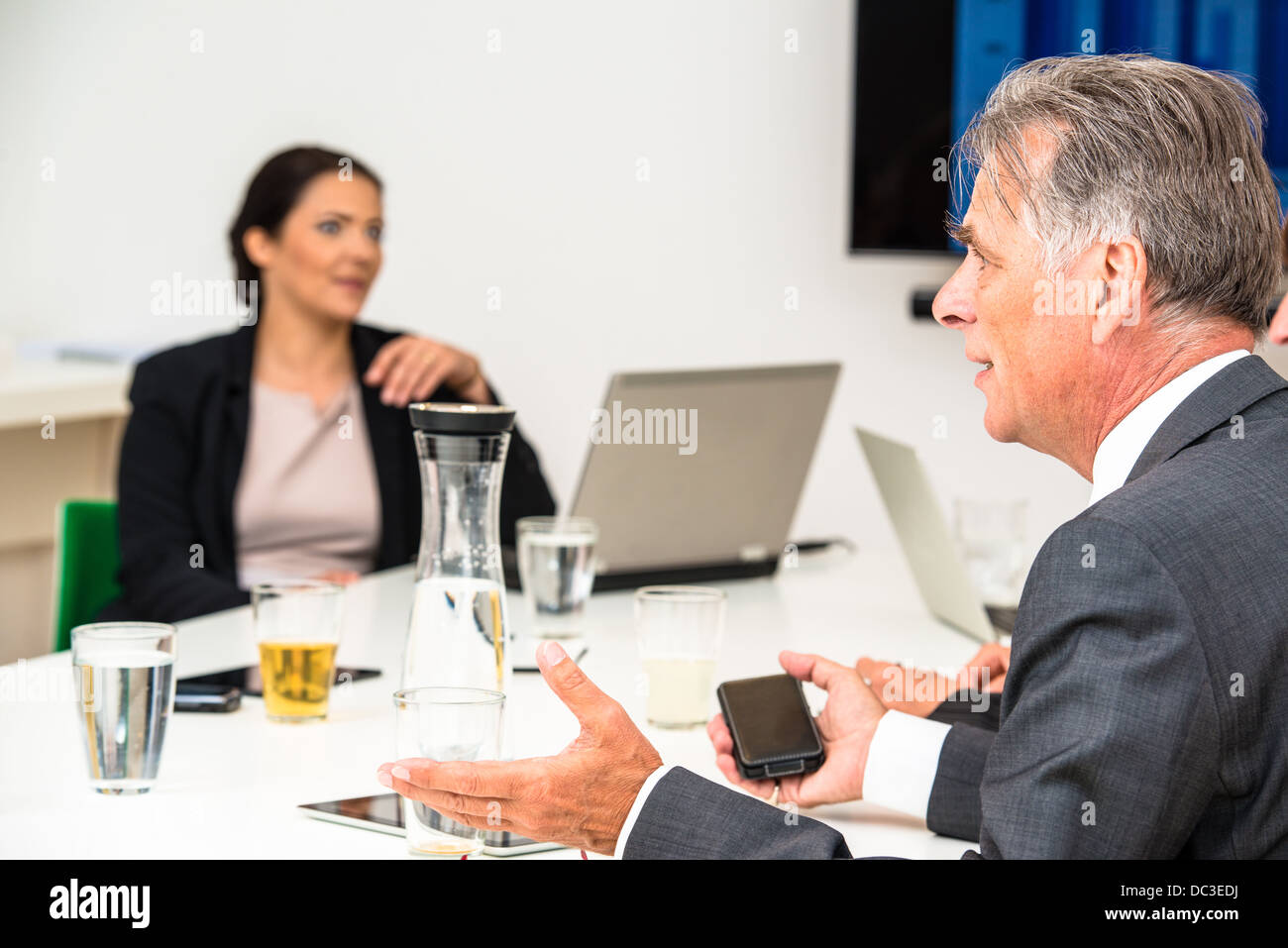 Mixed group in business meeting with laptops, projection screen, digital tablets and smartphones discussing the - Stock Image