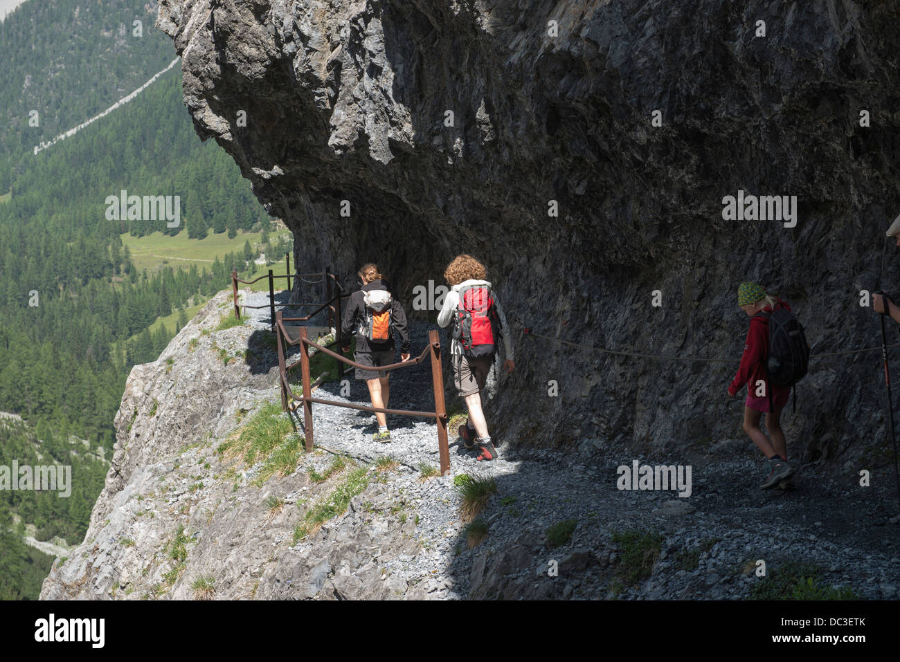 Wanderer auf Felsenweg in der Uinaschlucht - Hiker  on steep rock trail, Val d Uina - Stock Image