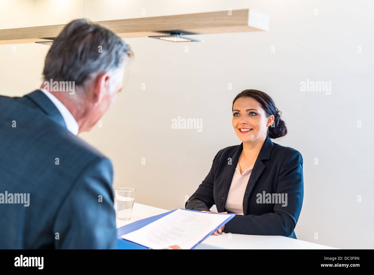 Recruiter (middle aged business man) checking the candidate, an attractive younger woman, during job interview - Stock Image
