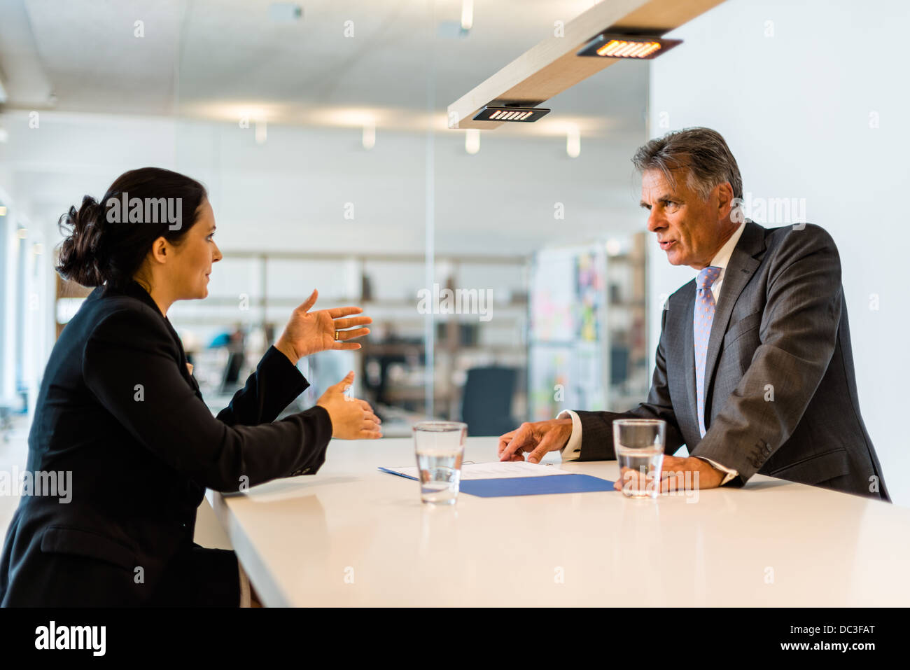 Recruiter (middle aged business man) checking the candidate, an attractive younger woman,during job interview with - Stock Image