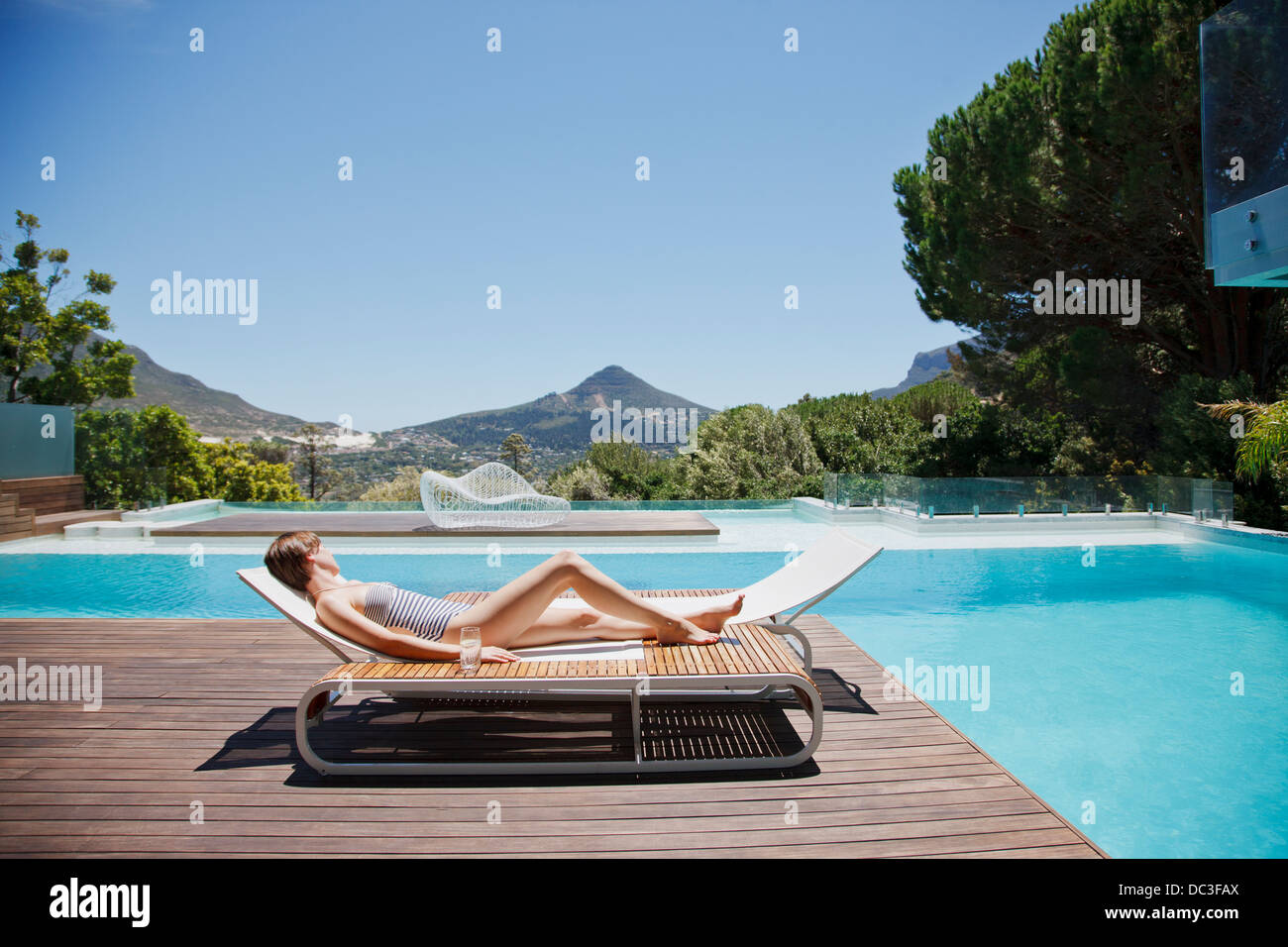 Woman Sunbathing On Lounge Chair Next To Luxury Swimming Pool With Mountain  View   Stock Image