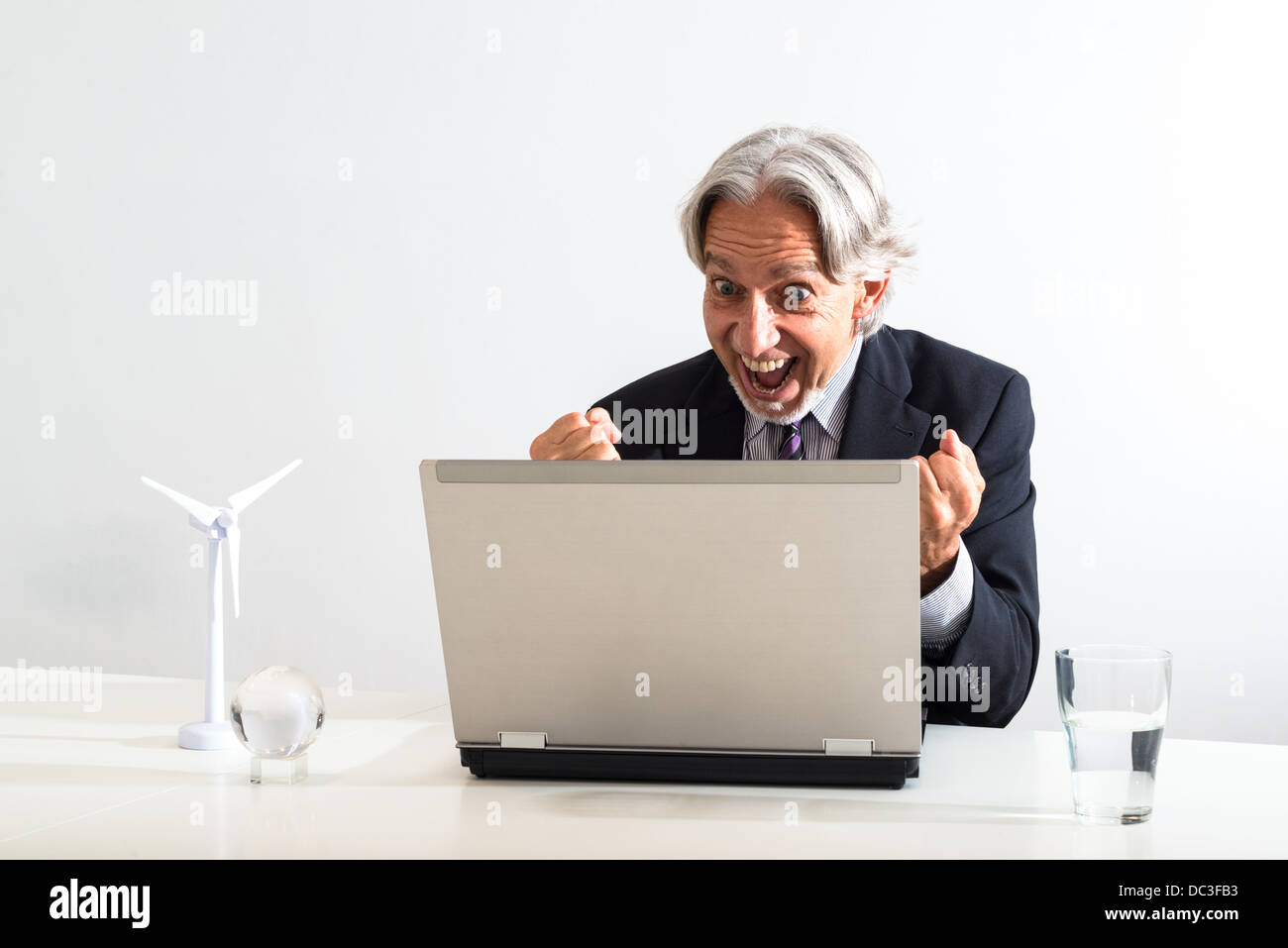 Successful Businessman Cheering Behind His Laptop In A