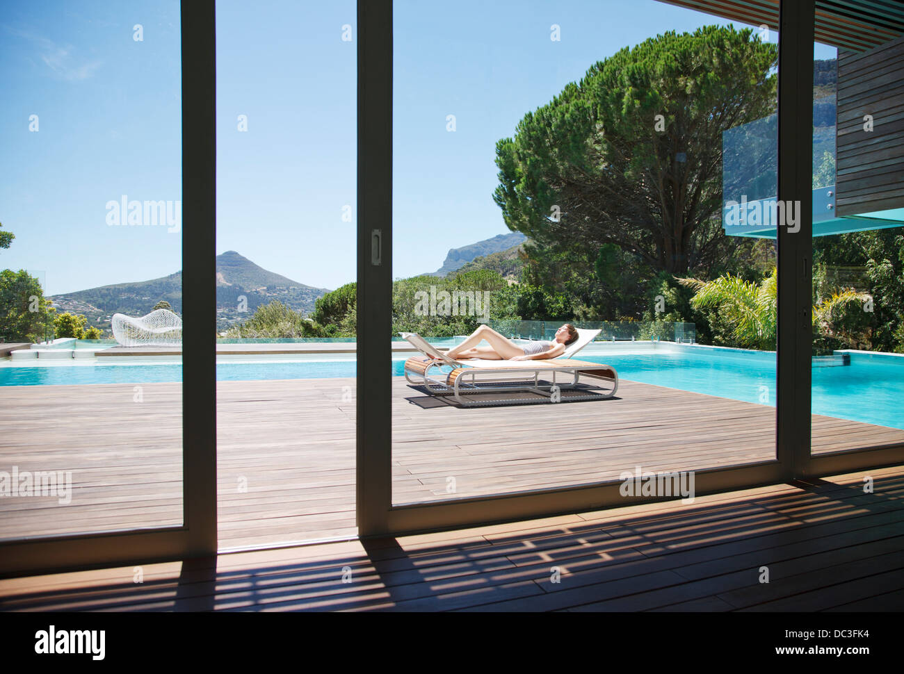 Woman sunbathing on lounge chair next to luxury swimming pool with mountain view Stock Photo