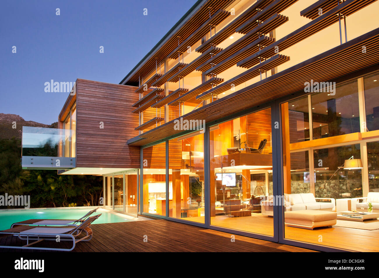 Swimming pool and modern house at night - Stock Image