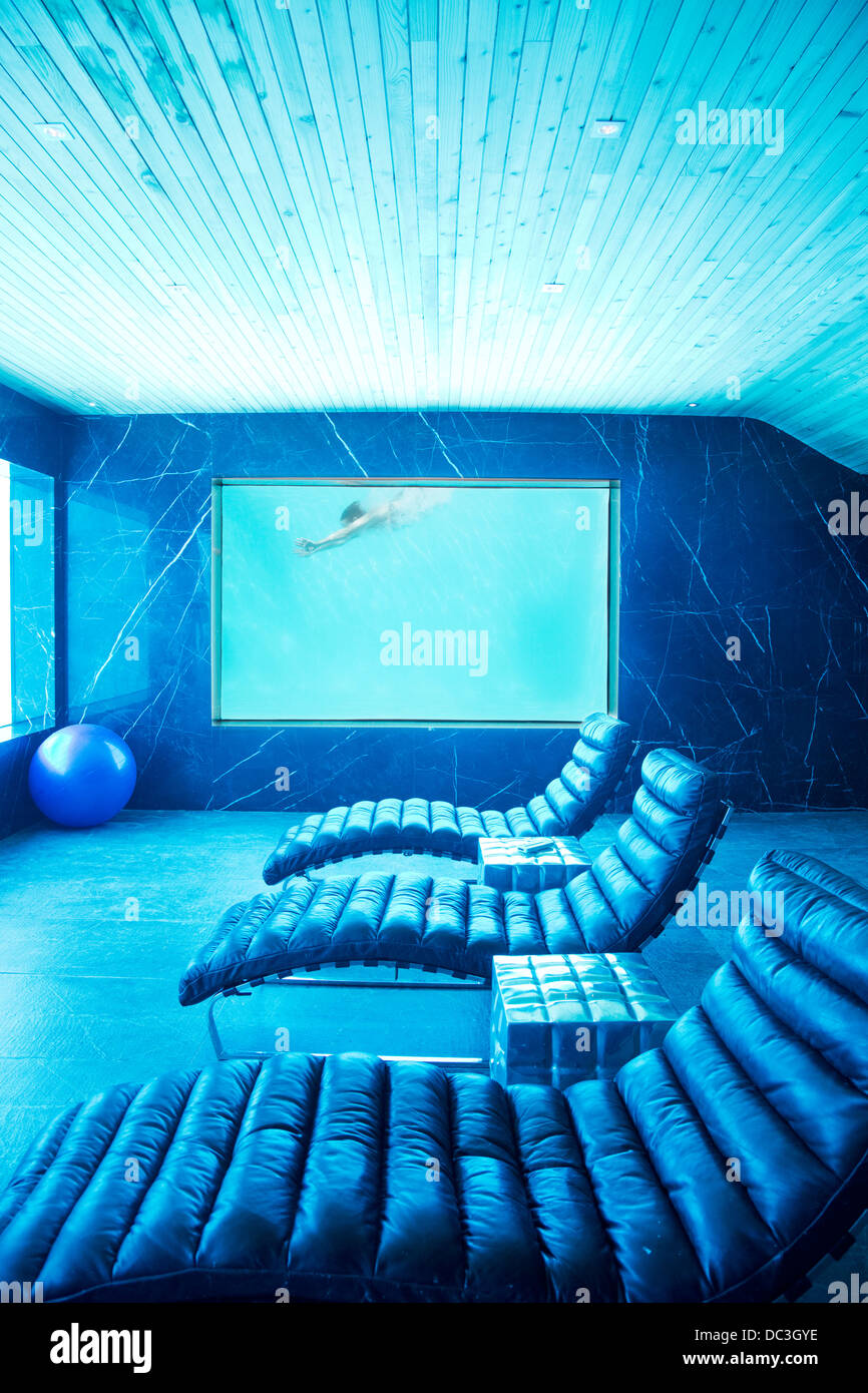 Room view of woman swimming underwater - Stock Image