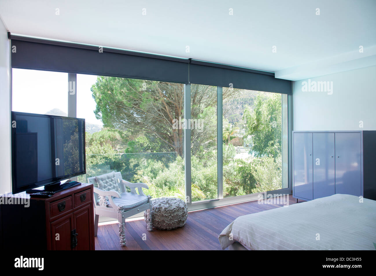 Modern bedroom with glass sliding doors - Stock Image
