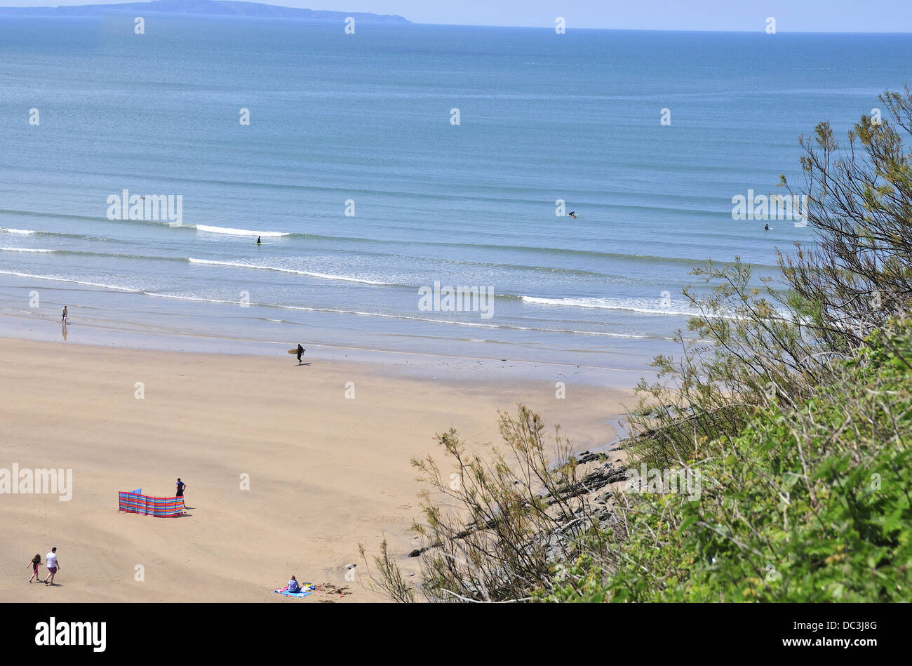 Surfers on the waves at  Saunton sands, A long stretch of sand with gentle shoal, one of north Devon famous surfing - Stock Image