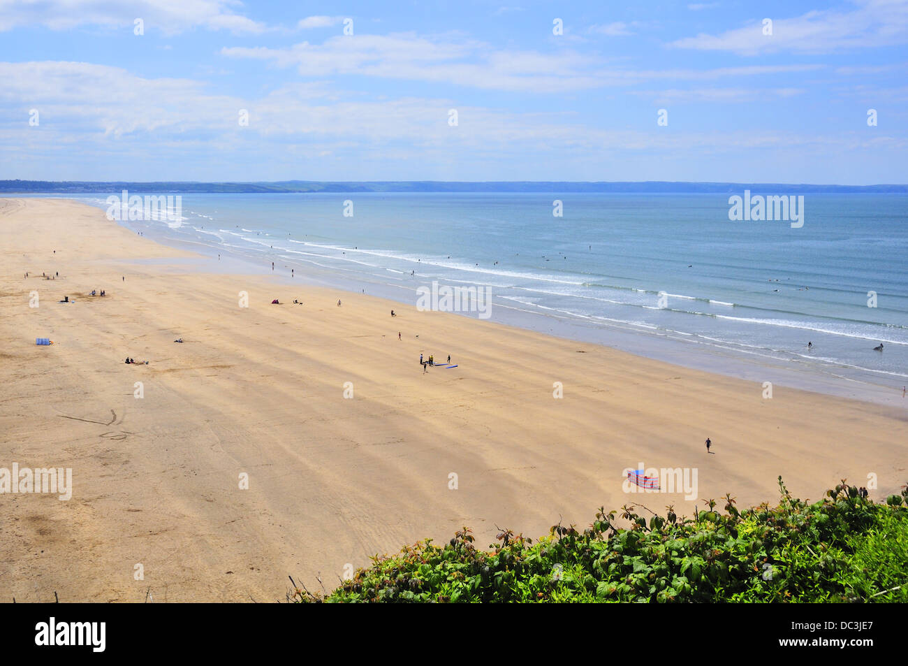 Surfers on the waves at  Saunton sands. A long stretch of sand with gentle shoal, one of north Devon famous surfing - Stock Image