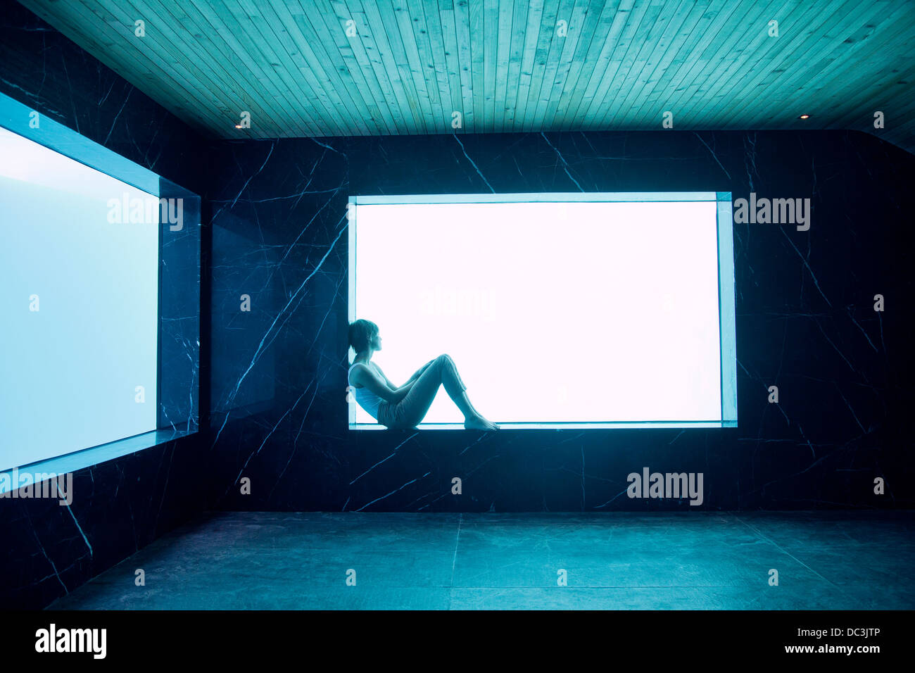 Woman sitting on ledge at window in pool room - Stock Image