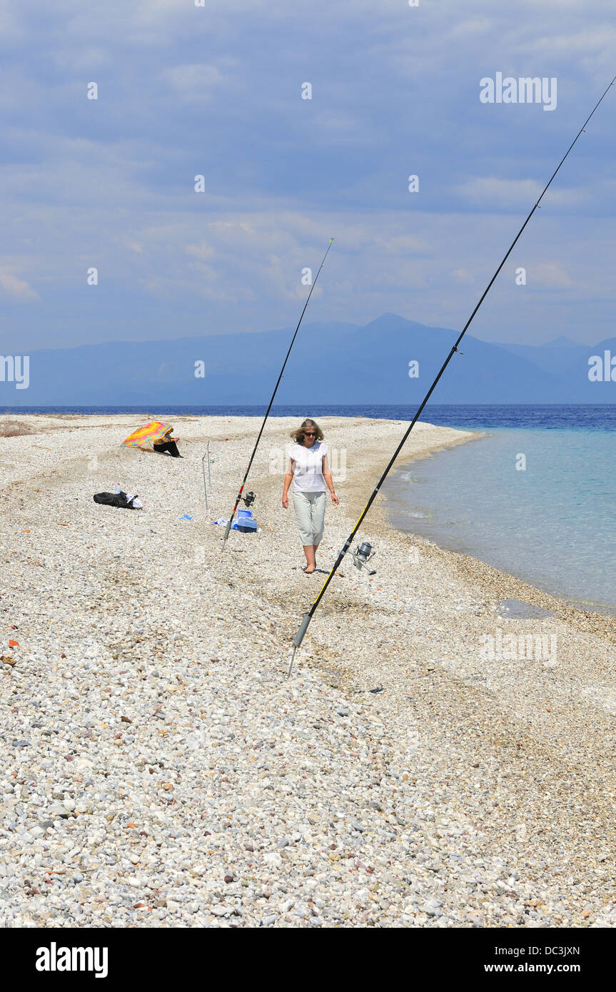 Beach scene near AKRATA BEACH on the northern  coast  on the Peloponnese Greece with lady walking on foreshore past - Stock Image