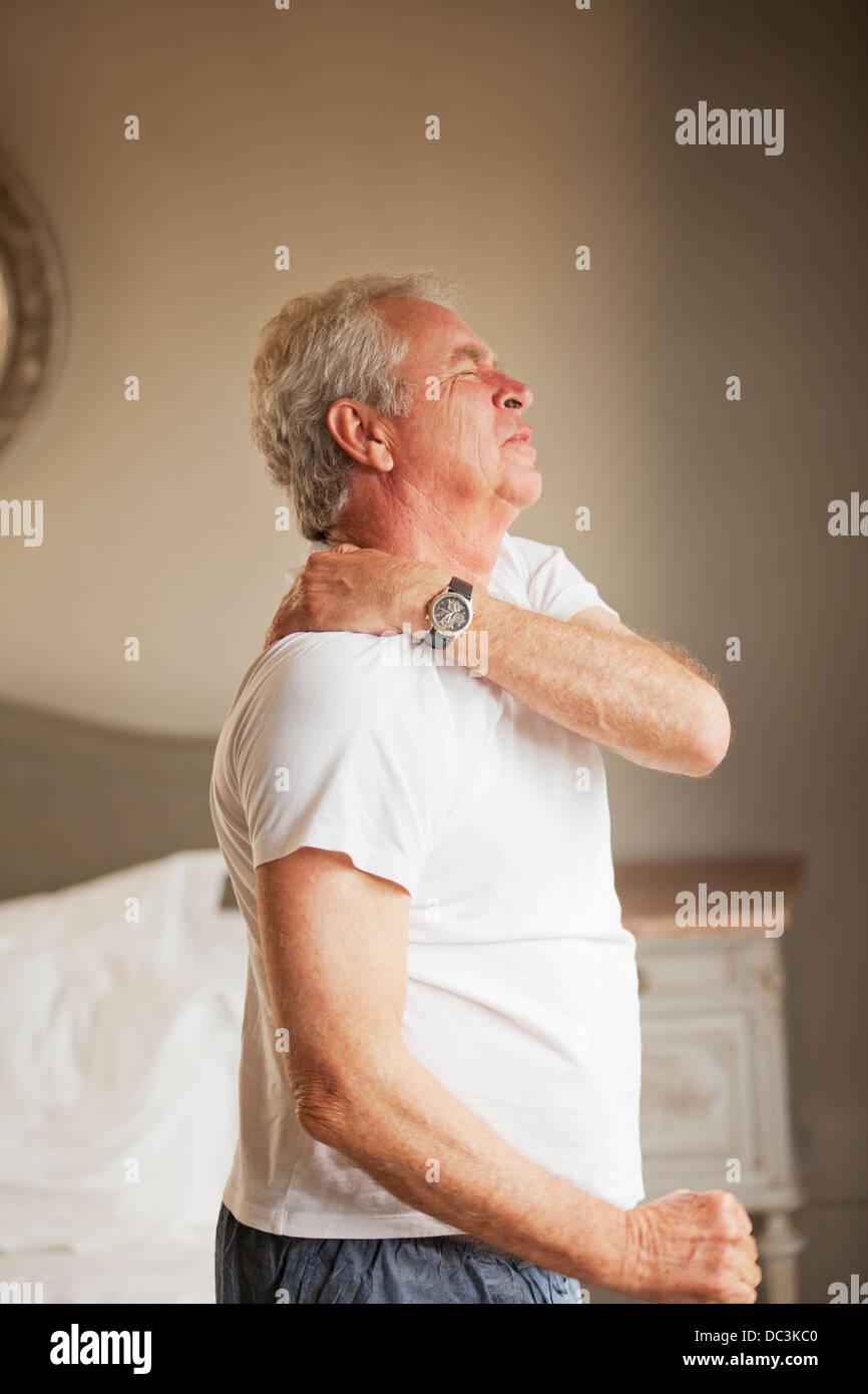 Senior man holding shoulder in pain - Stock Image