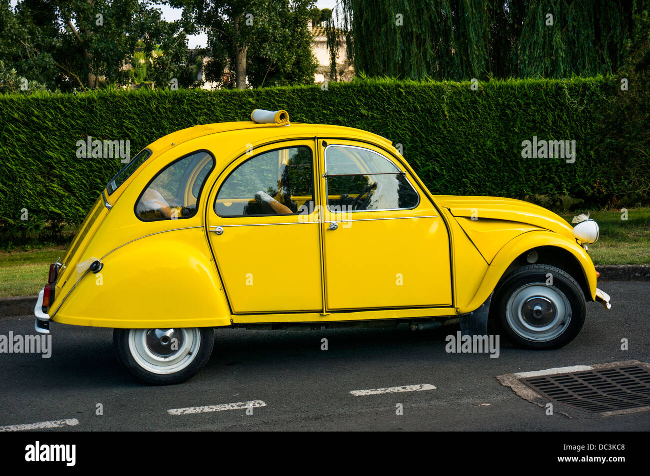 An old, bright yellow, iconic, Citroen 2CV car, parked in Amboise in the Indre-et-Loire department in central France. - Stock Image