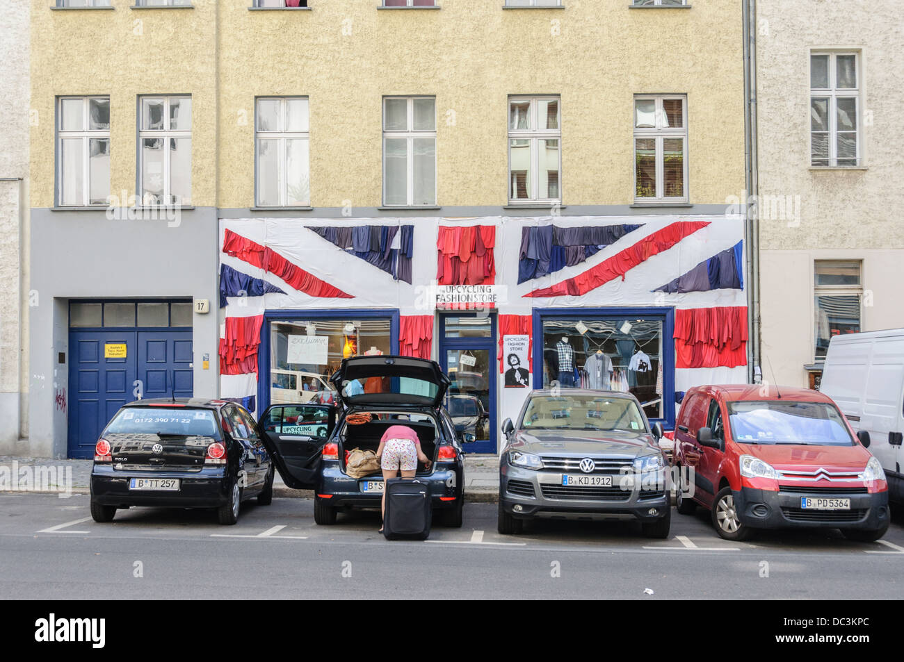Upcycling Fashion Store with Union Jack – Woman in shorts unloads her car in front of a British fashion store in Stock Photo