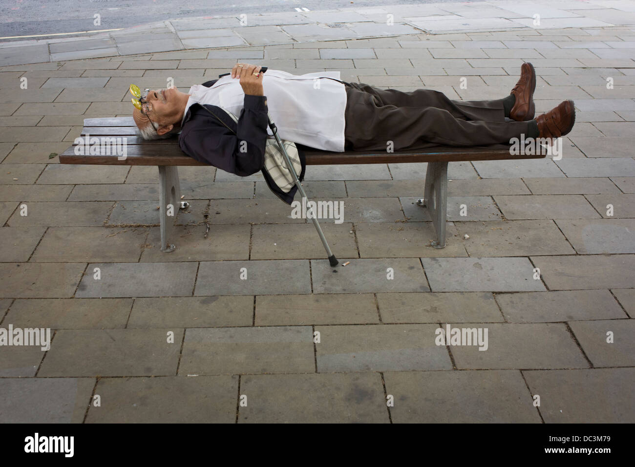 Guarding his walking stick, an elderly gentleman sleeps on a city street bench in central London, his hinged glasses - Stock Image