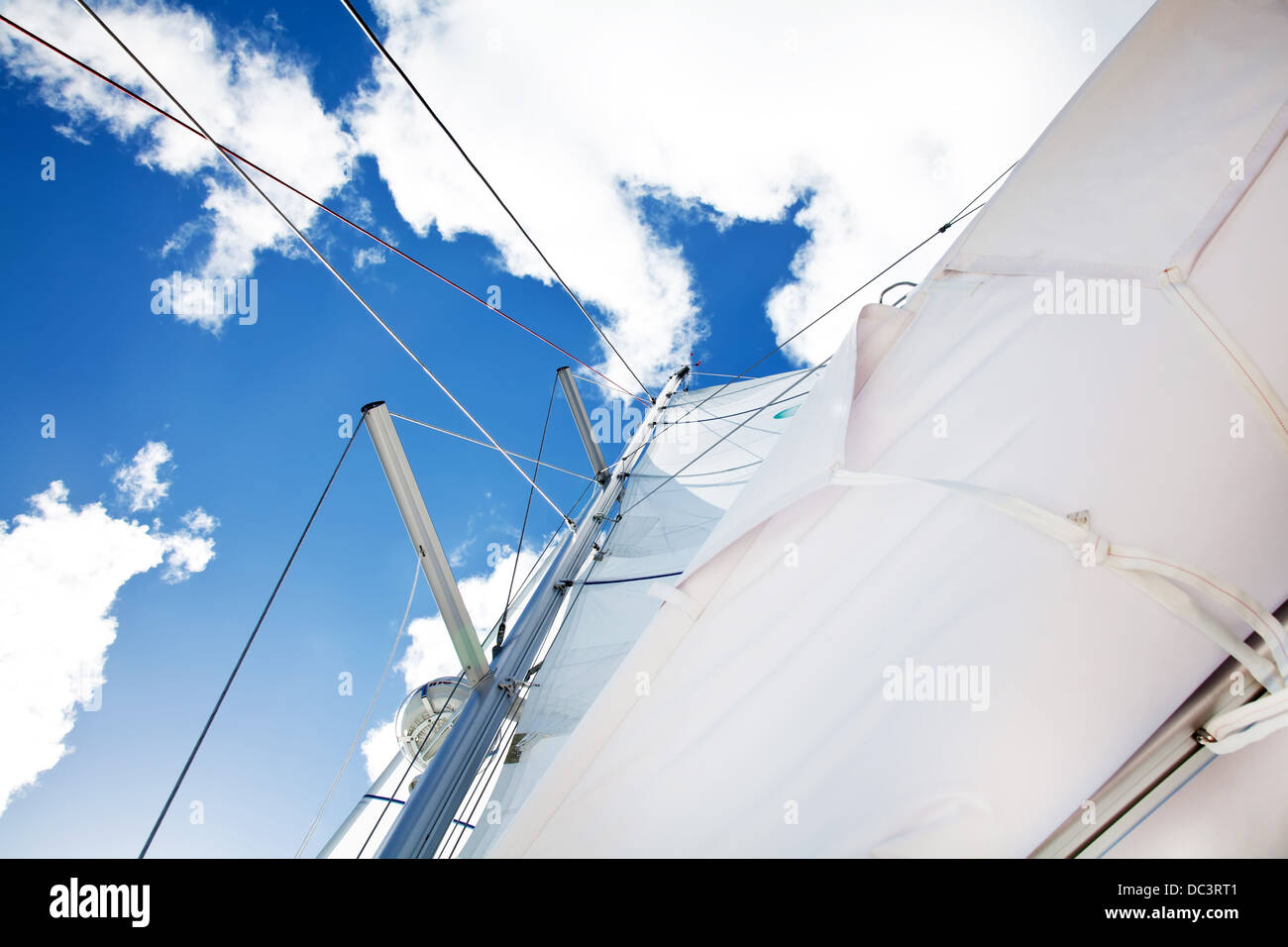 Sail of a sailing boat over bright bue sky - Stock Image