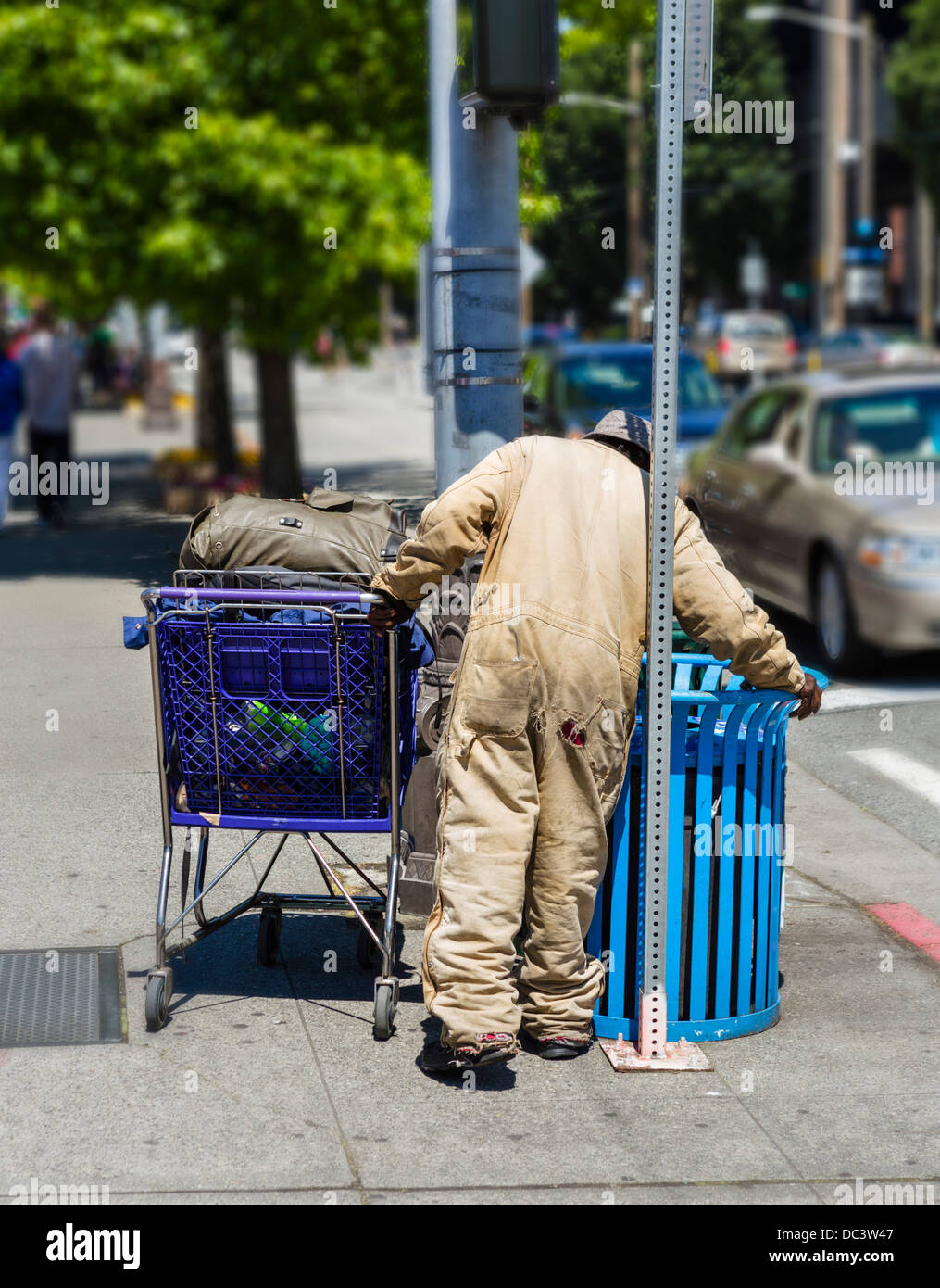 Homeless man with a shopping cart scavenging in a trash can, Seattle, Washington, USA - Stock Image