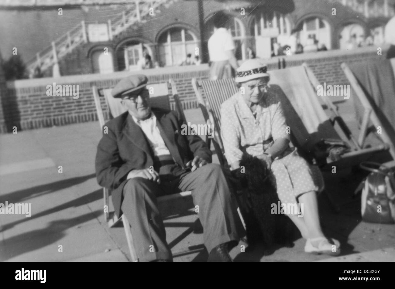 An elderly couple from the 1930's sitting in deck chairs near the famous 'Slip' on Swansea Beach. - Stock Image