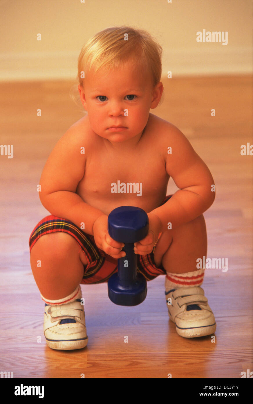 Toddler boy lifts hand weight - Stock Image