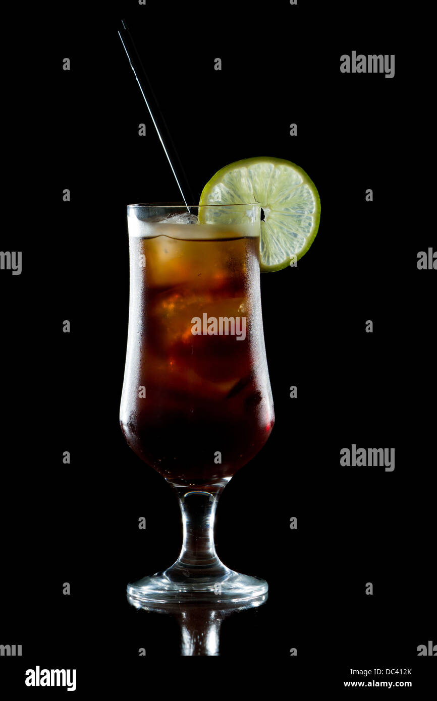 cuba libre, rum and cola cocktail served in a stem glass with a lime garnish - Stock Image