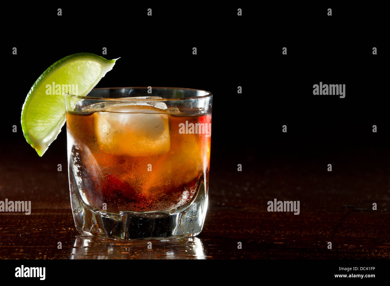 cuba libre, rum and cola cocktail served in a short glass with a lime garnish - Stock Image