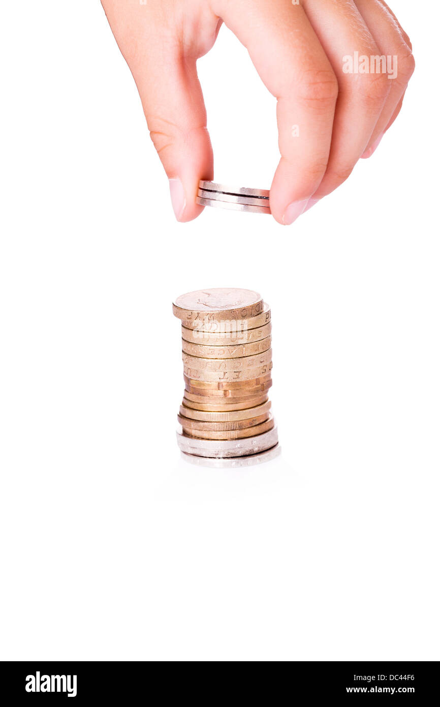 Hand adding coins to stacks of money. Thriftiness concept - Stock Image