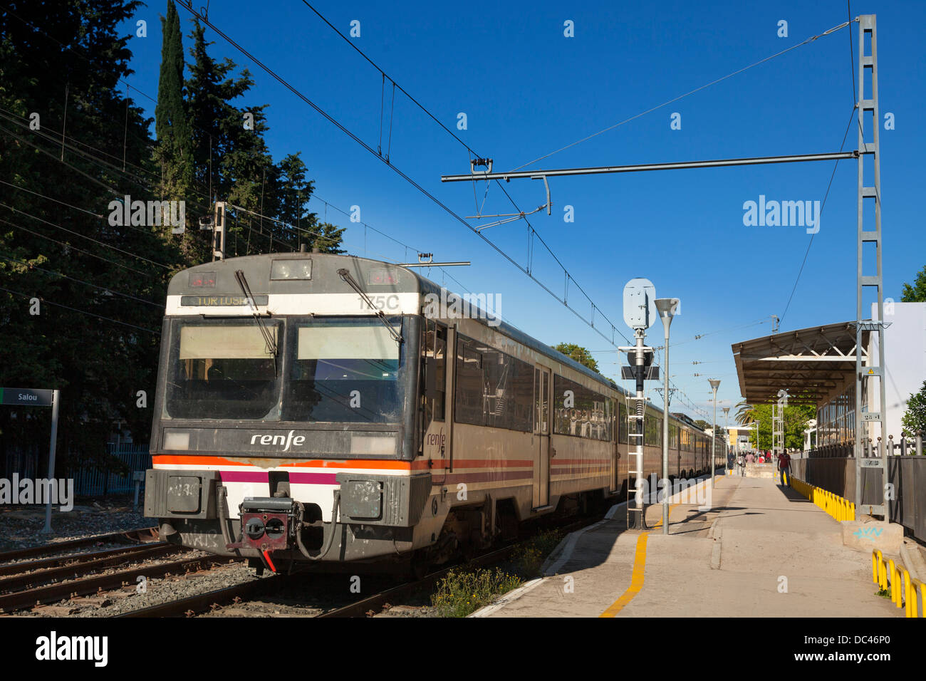 Renfe train at Salou Station platform with overhead power lines. - Stock Image