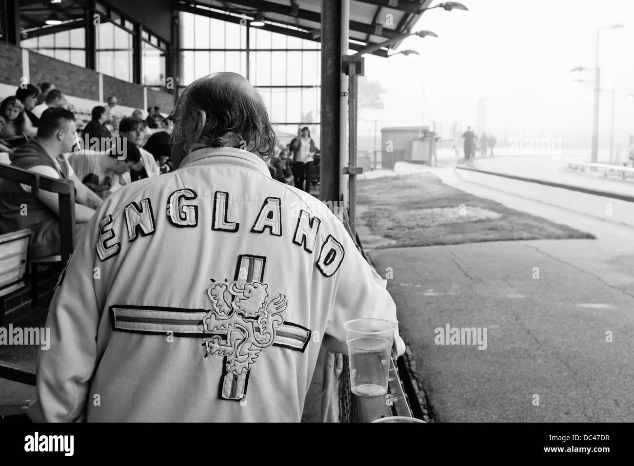 Spectator wearing England Jacket drinking and watching greyhound race - Stock Image