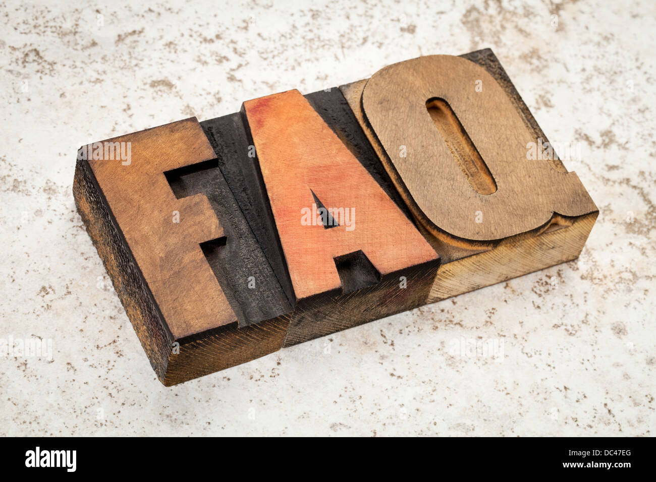 frequently asked questions - FAQ acronym - text in vintage letterpress wood type on a ceramic tile background - Stock Image