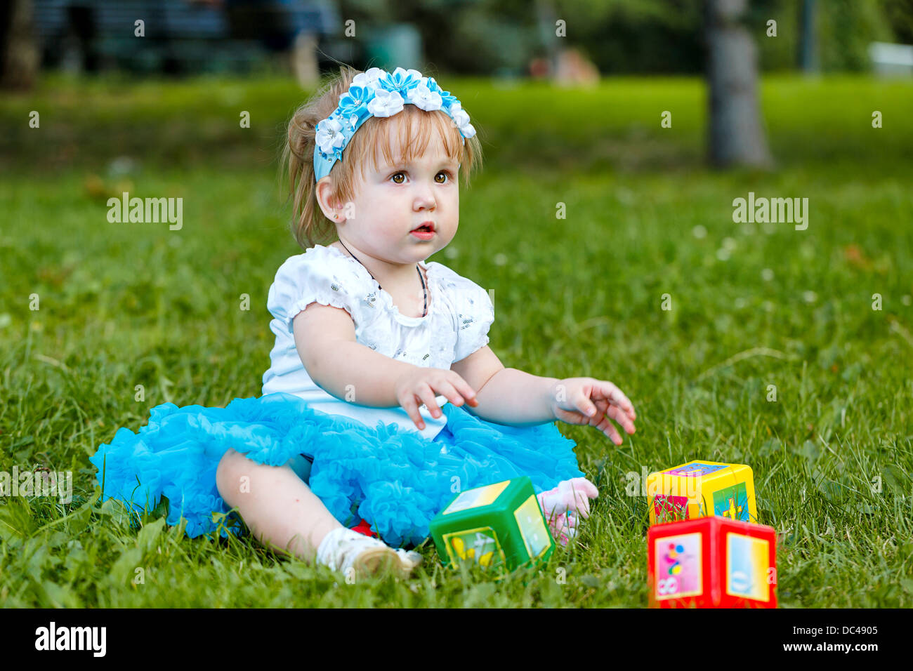 Little girl sitting on the grass and playing with dice in the park - Stock Image