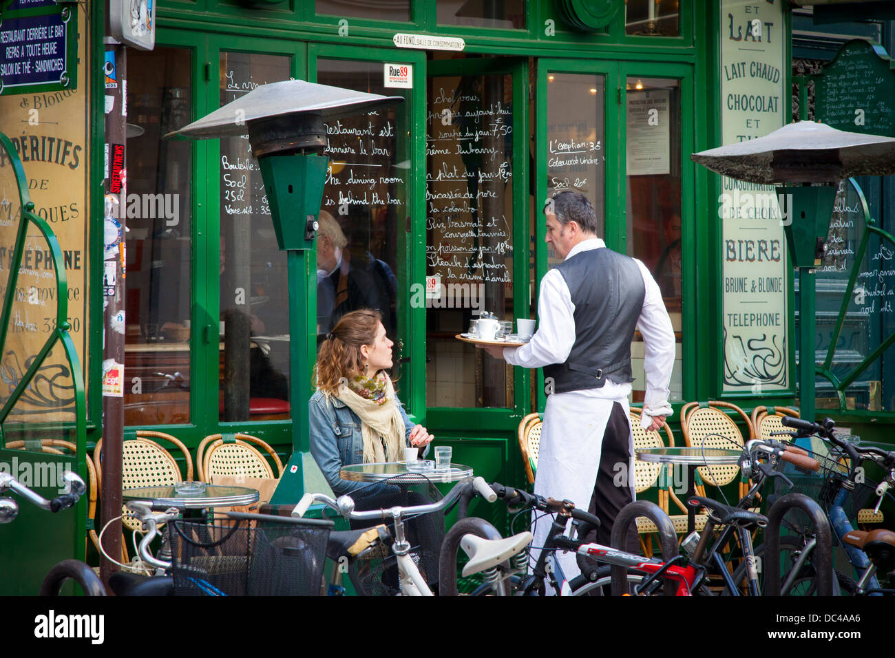 Waiter and customer at a cafe in les Marais, Paris France - Stock Image