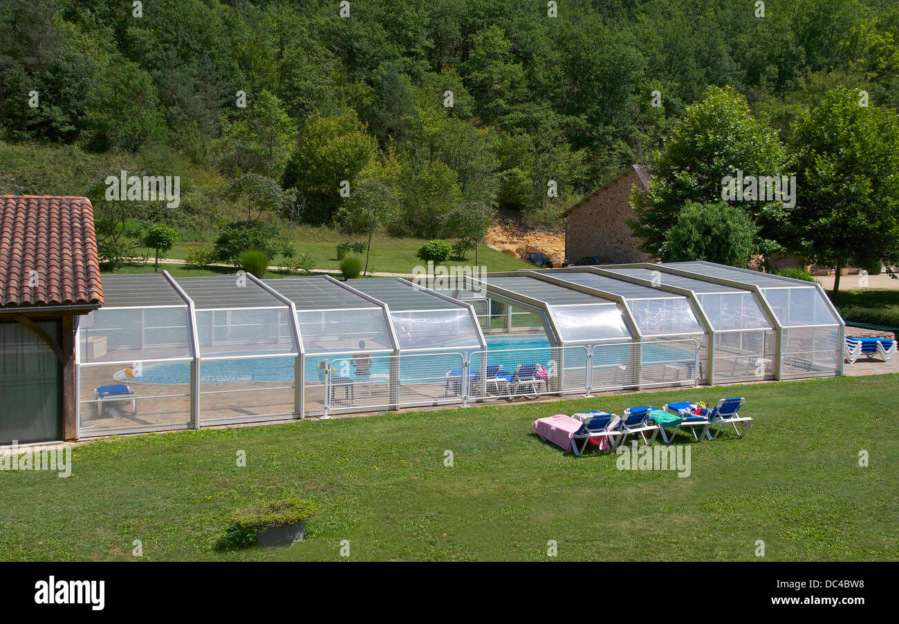 Outdoor swimming pool, with retractable mobile roof. Dordogne, France. - Stock Image