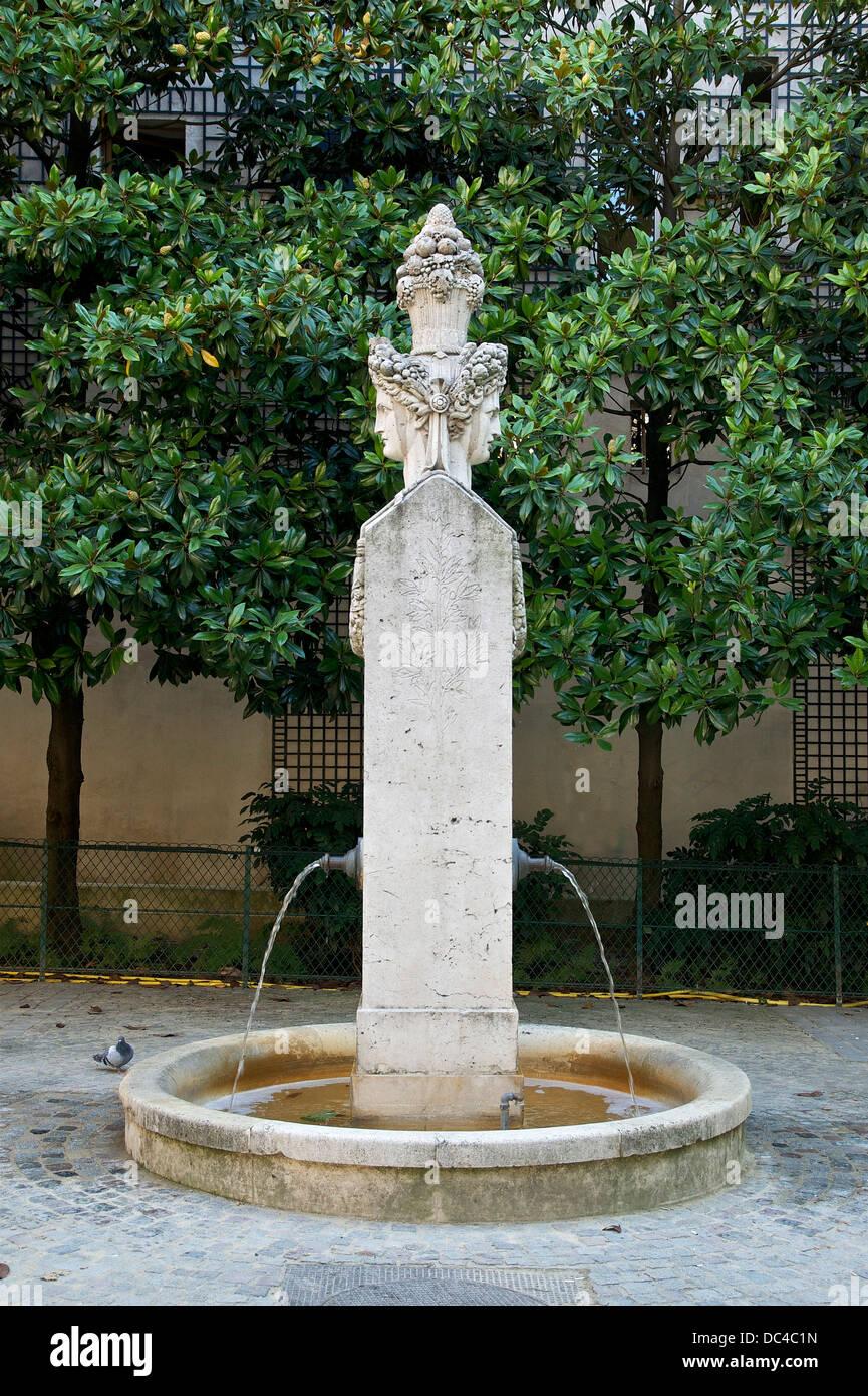 the Fontaine du Marché-aux-Carmes, square Gabriel Pierné in Paris, 6th arrondissement. The face at right - Stock Image